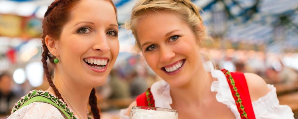 Junge Frauen feiern auf dem Oktoberfest in Bayern zur Musik einer Stimmungsband