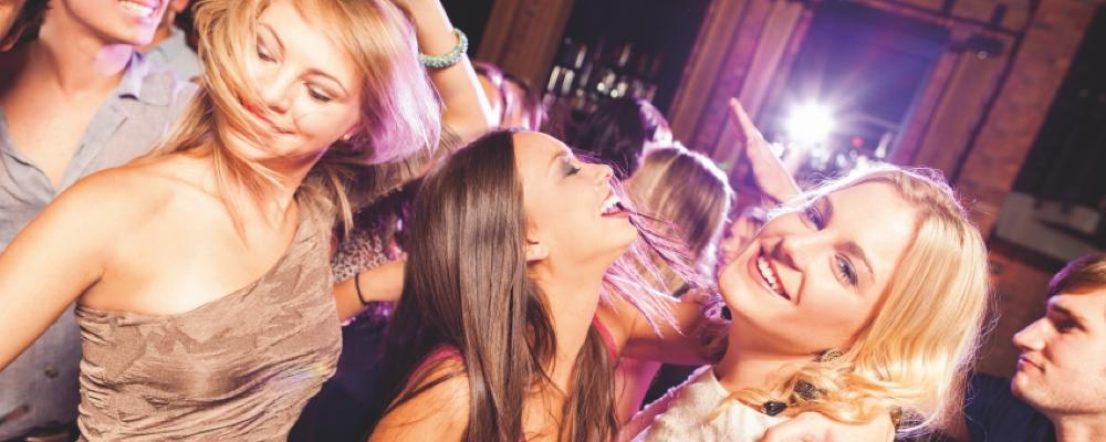 Partygäste tanzen ausgelassen zur Musik einer Partyband