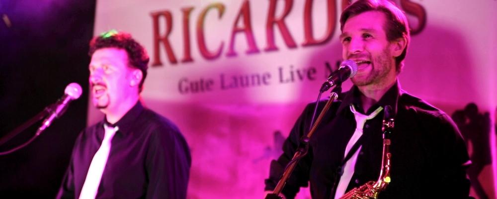 Zwei Bandmitglieder der Liveband singen